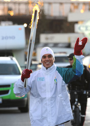 Steven Lopez, Olympic Tae Kwon Do champion, carries the Olympic Torch to Vancouver.